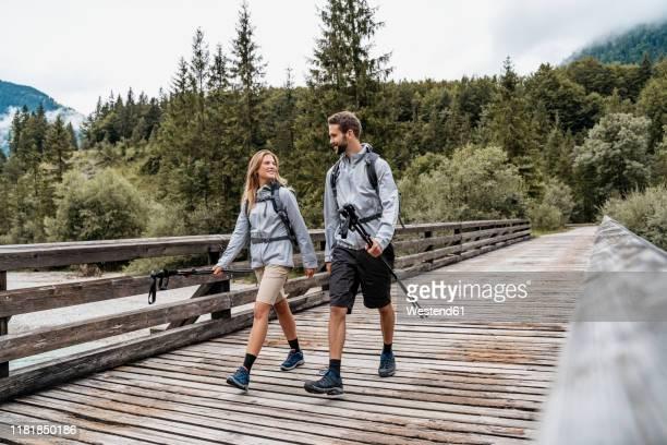 young couple on a hiking trip walking on wooden bridge, vorderriss, bavaria, germany - wandern stock-fotos und bilder