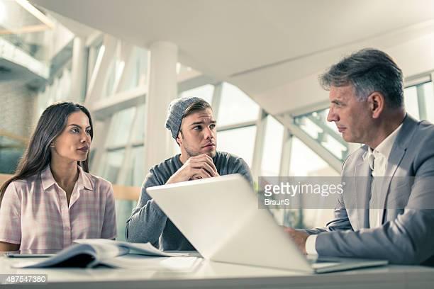 Junges Paar auf einer Tagung mit Immobilienmakler.