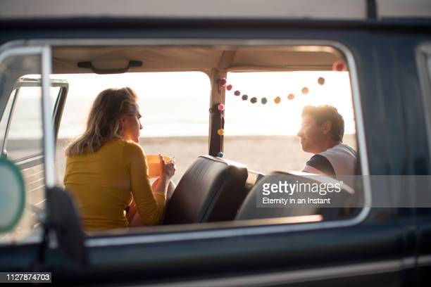 ws young couple on a road trip in a vintage camper van - camping stock-fotos und bilder