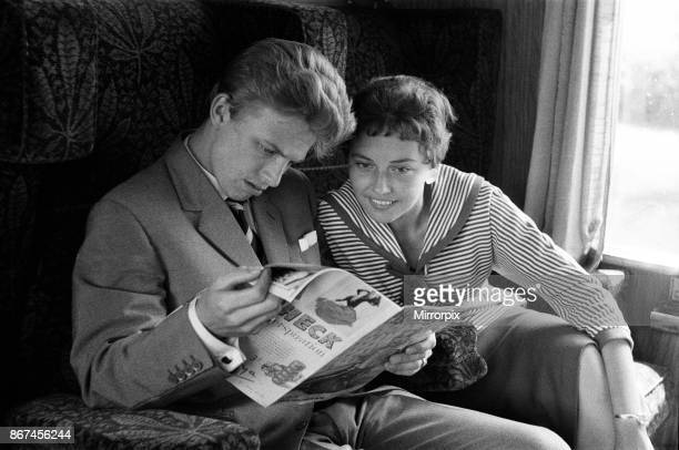Young couple on a train, reading a copy of Photoplay magazine. Llandudno, Conwy County Borough, Wales, 16th July 1958.