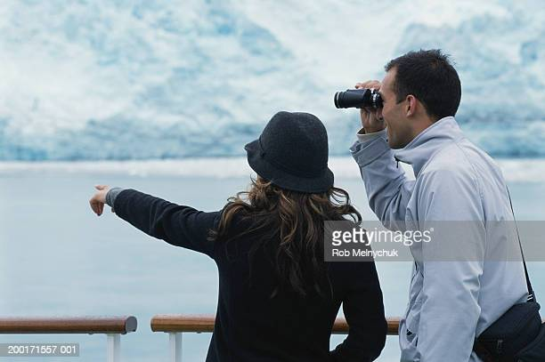 Young couple on balcony of ship, man using binoculars, woman pointing