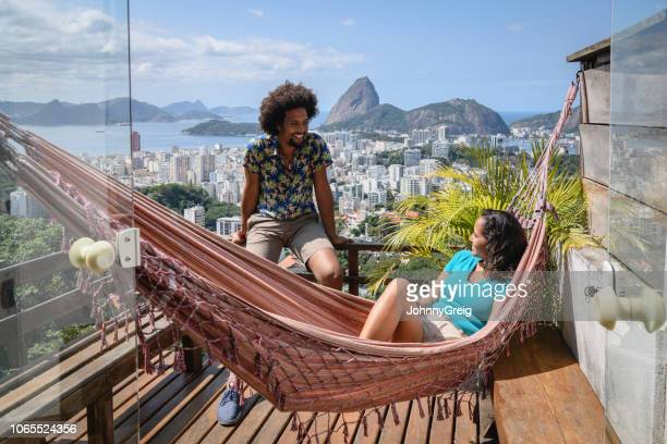 junges paar auf balkon mit blick auf rio im hintergrund - rio de janeiro stock-fotos und bilder