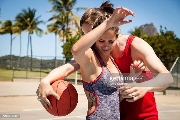 Young couple on basketball court in front of Sugarloaf mountain, Rio De Janeiro, Brazil