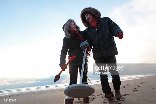 young couple on beach in witer with metal detector