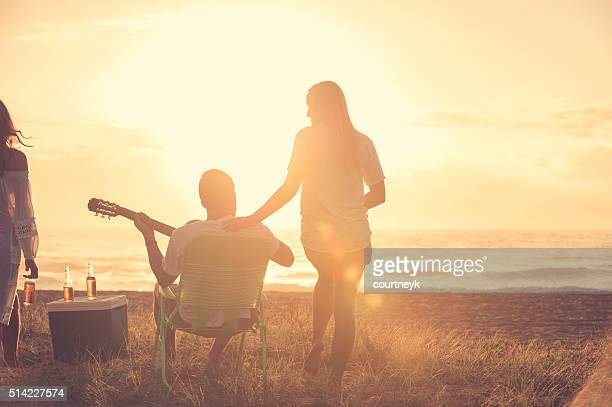 Young couple on beach looking at sunset with guitar.