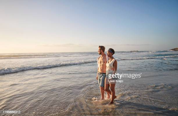 young couple on beach - female hairy chest stock pictures, royalty-free photos & images