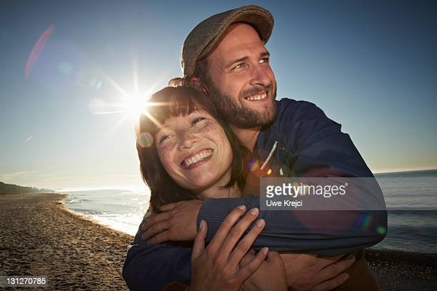 Young couple on beach, smiling, close up