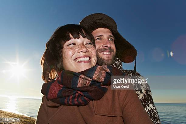 Young couple on beach, smiling, winter clothing