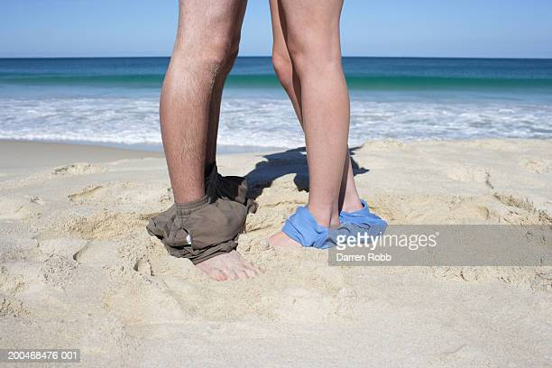 Young couple on beach, swim wear around ankles, low section, side view
