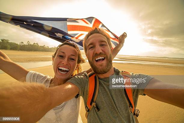 Young couple on beach take selfie portrait with Australian flag