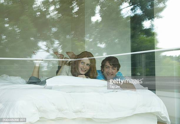 Young couple on bed, looking out of window, trees reflected in glass