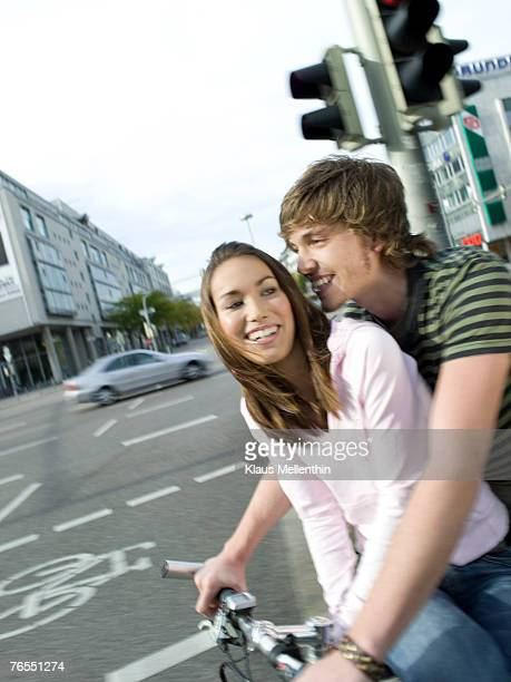 Germany, teenage couple (16-17) riding on bicycle, blurred motion
