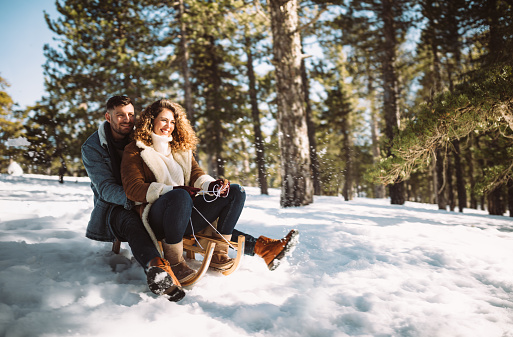 Young couple on Christmas holidays riding sledge in the snow 962782452