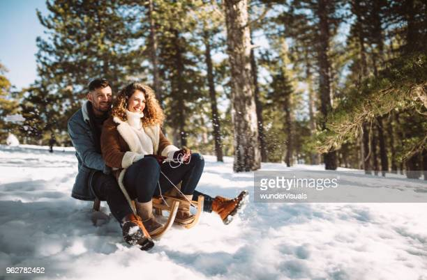 young couple on christmas holidays riding sledge in the snow - sled stock pictures, royalty-free photos & images