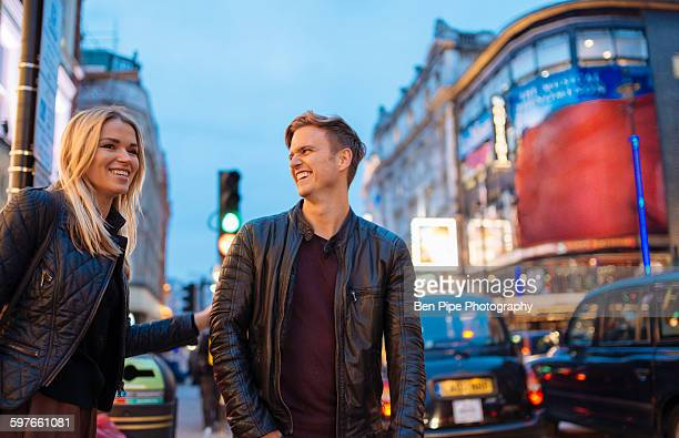 young couple on city street at night, london, england, uk - shaftesbury avenue london stock photos and pictures