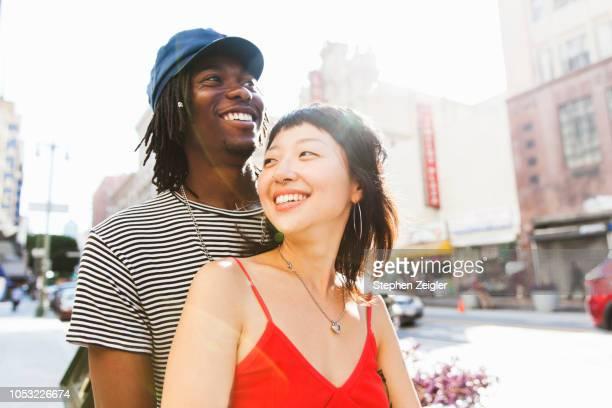 young couple on city street - jeune couple photos et images de collection