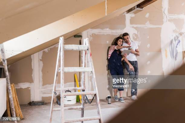 young couple on construction site of their new home, using digital tablet - reform stock pictures, royalty-free photos & images