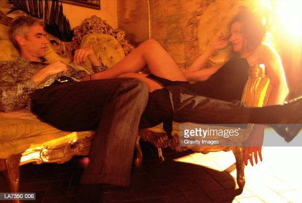 young couple on couches, woman resting feet on man (enhancement) - feticismo foto e immagini stock