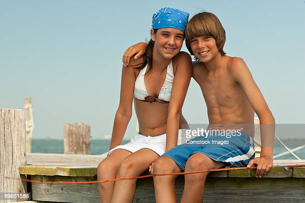 young couple on dock by water - 12 13 jahre fotos boys stock-fotos und bilder