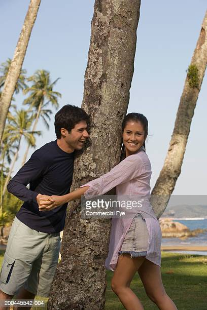 young couple on either side of palm tree, man grabbing woman's hand - palm sunday photos et images de collection