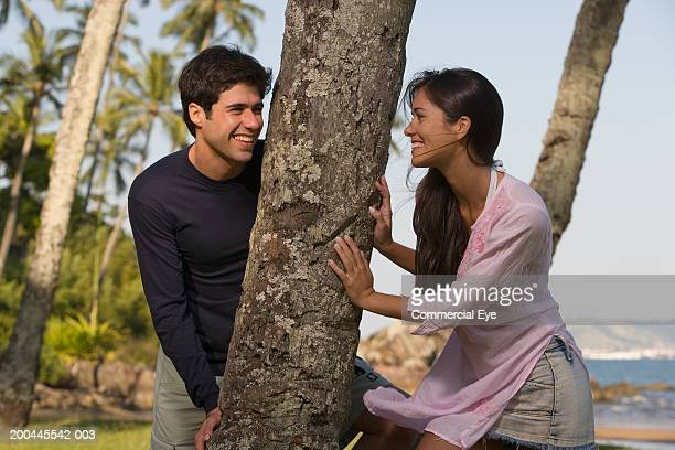 young couple on either side of palm tree smiling at each other - palm sunday photos et images de collection