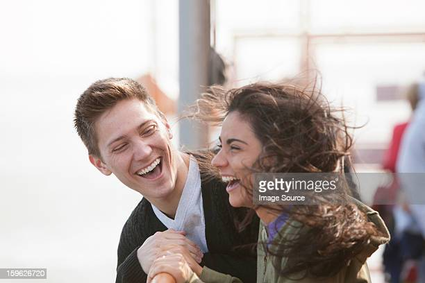 Young couple on ferry, laughing