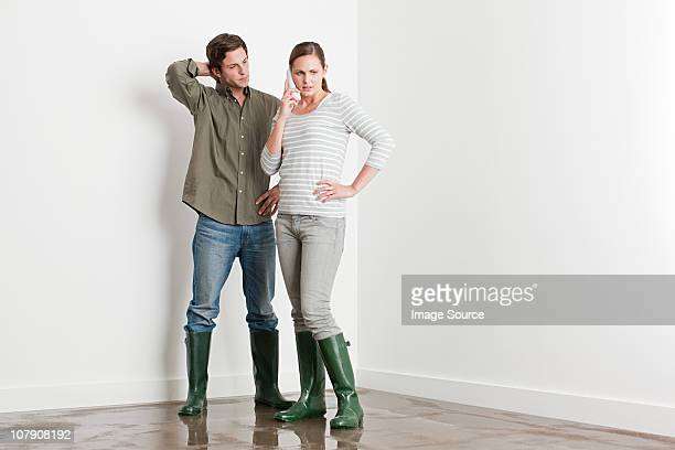 young couple on flooded floor - flooding stock photos and pictures
