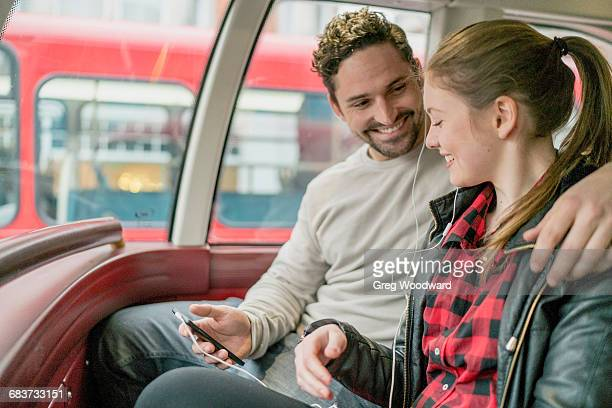 Young couple on front seat of double-decker, Kings Road, London, UK