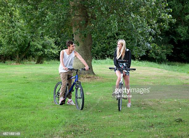young couple on grass with bicycles - アマシャム ストックフォトと画像