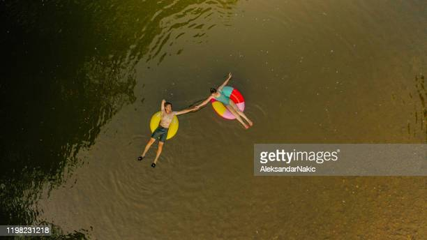young couple on inflatable rings in the river - tube stock pictures, royalty-free photos & images