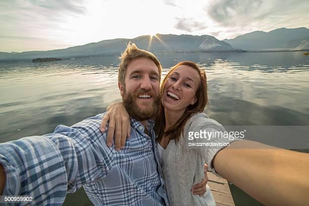 Jeune couple sur la jetée au-dessus du lac, prend une photo de selfie