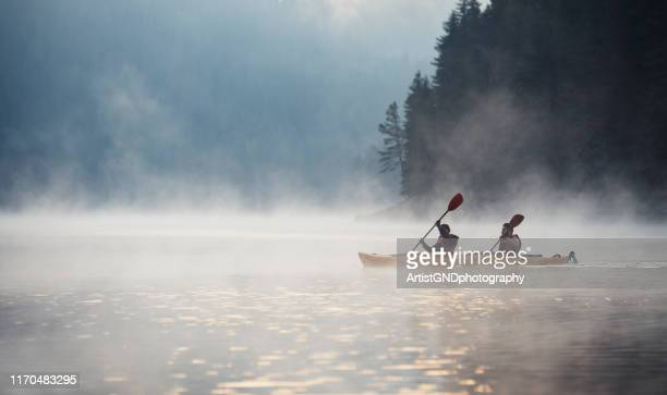 young couple on kayaking adventure in mountain lake. - kayak stock pictures, royalty-free photos & images