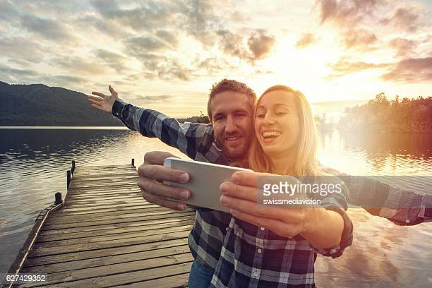 Young couple on lake pier take selfie using smart phone
