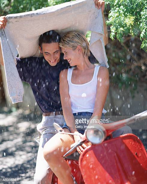 Young couple on motor scooter, shelterd from rain under mans sweater