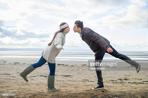 young couple on one leg, brean sands, somerset, england - sean malyon stock pictures, royalty-free photos & images