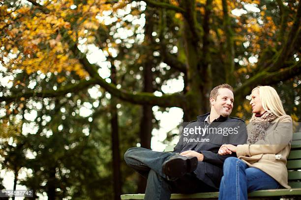 young couple on park bench and autumn leaves - heterosexual couple stock pictures, royalty-free photos & images