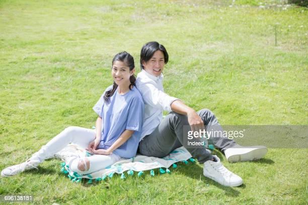 young couple on picnic blanket - 背中合わせ ストックフォトと画像
