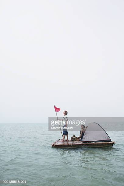 Young couple on raft, man holding flag, woman emerging from tent