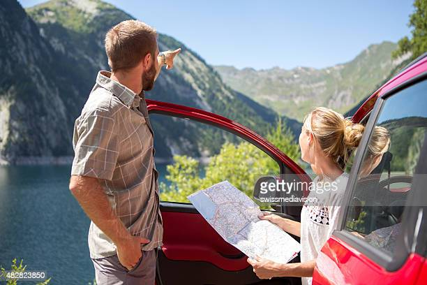 Young couple on road trip reading a map for directions-Summer