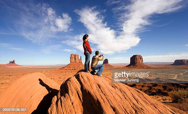 Young couple on rock, man taking photograph