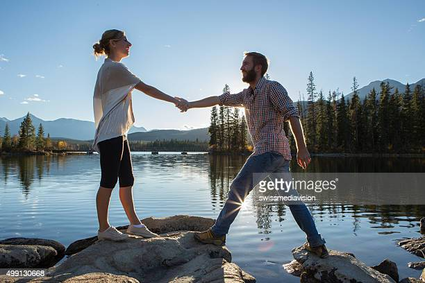 Young couple on rocks by the lake holding hands.