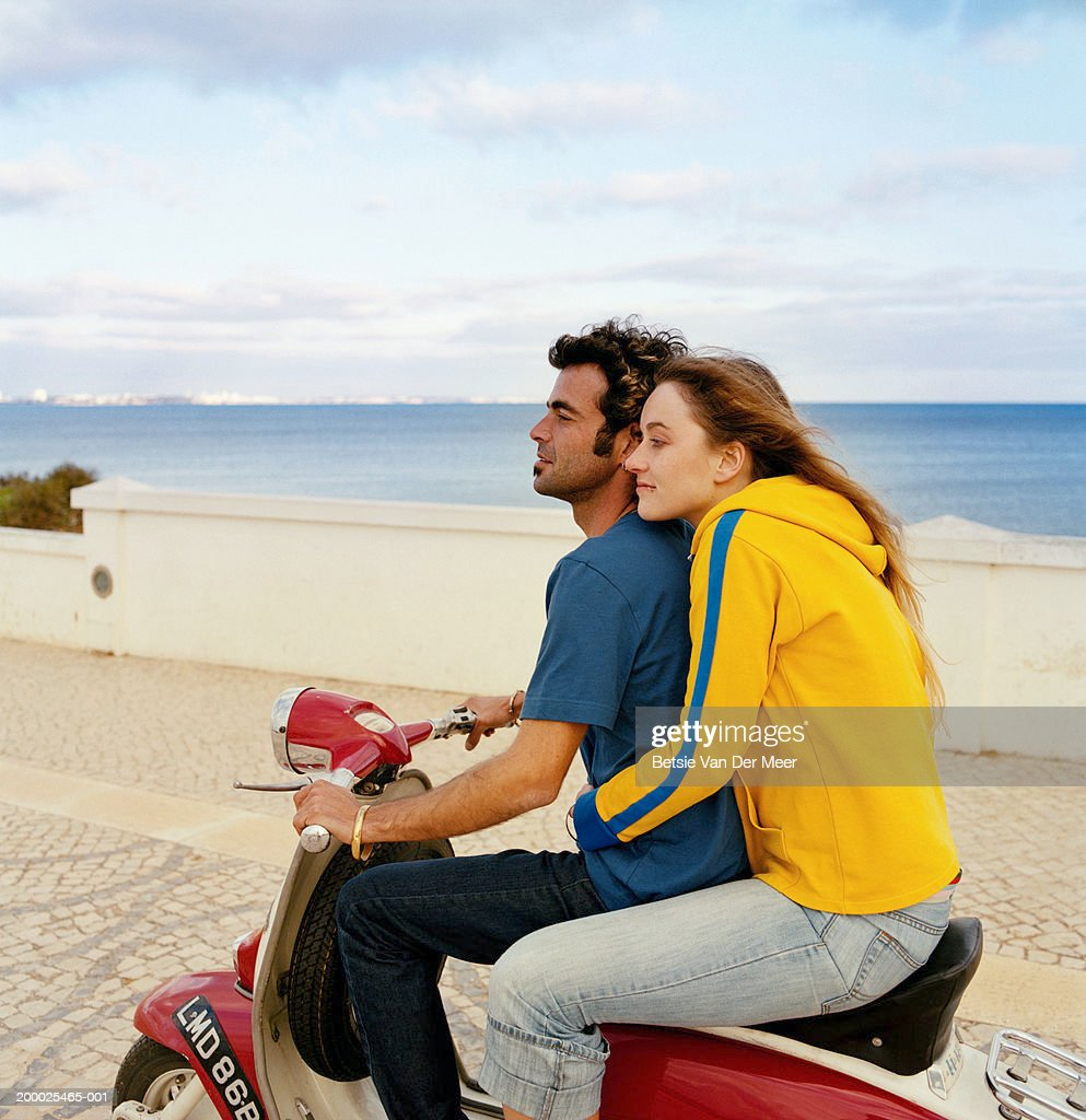 Young couple on scooter by sea : Stock-Foto