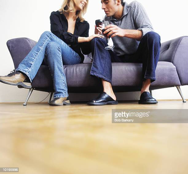 young couple on sofa drinking red wine - heterosexuelles paar stock-fotos und bilder