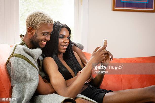 young couple on sofa, looking at smartphone - transgender man stock photos and pictures