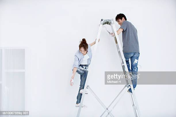 Young couple on step ladder, painting new home