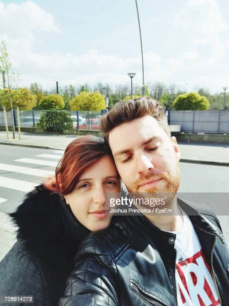 Young Couple On Street In City Against Sky