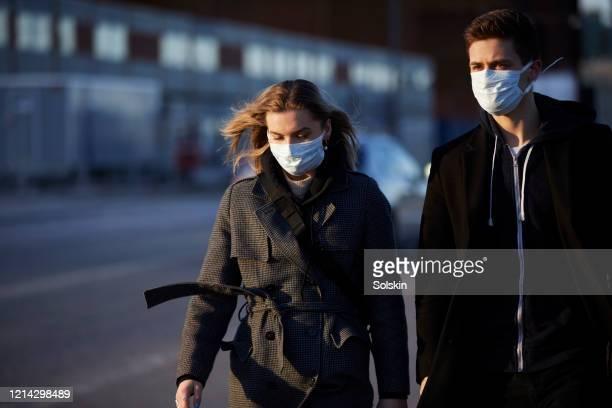 young couple on street wearing a virus protective face mask - munskydd ensam bildbanksfoton och bilder