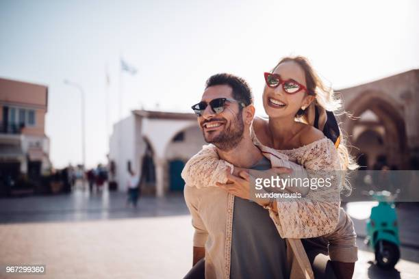 young couple on summer vacations having fun with piggyback ride - spain italy stock pictures, royalty-free photos & images