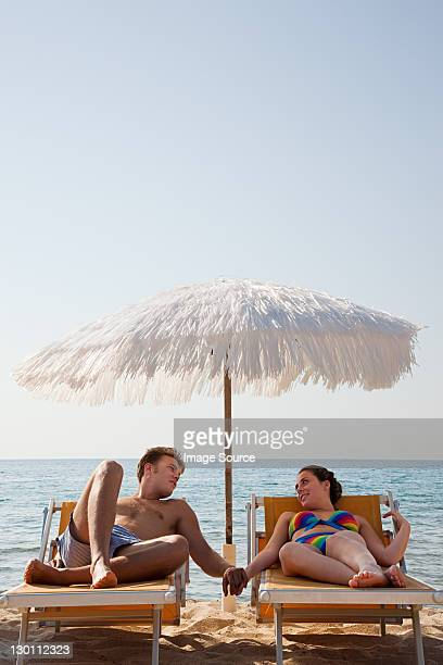 young couple on sun loungers holding hands - sun lounger stock pictures, royalty-free photos & images
