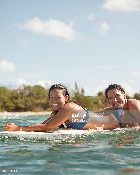 young couple on surfboard in water together - haleiwa - fotografias e filmes do acervo